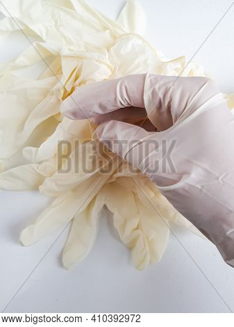 Hand In White Medical Gloves And Pile Of White Medical Gloves