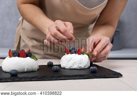Process Of Making Berry Cake. Womens Hands Decorate Meringue. Anna Pavlova Cake.