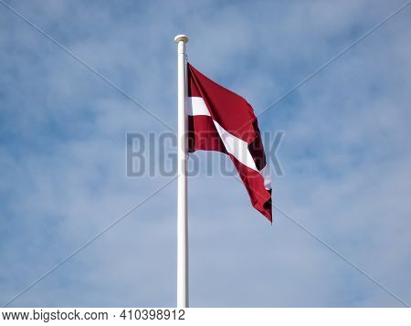 The National Flag Of Latvia In The Wind With Blue Cloudy Sky. Exact Colours Of Latvian Flag - Carmin