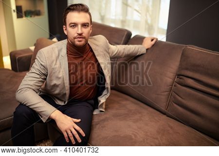 Handsome middle-aged man in elegant smart casual clothes having a rest at home. Success and well-being.