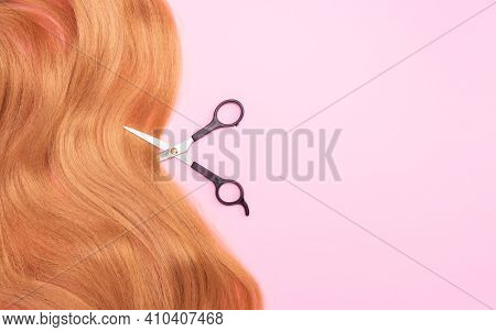Brown Artificial Hair On A Pink Background And Scissors. The Concept Of A Hair Salon, Hair Cutting.