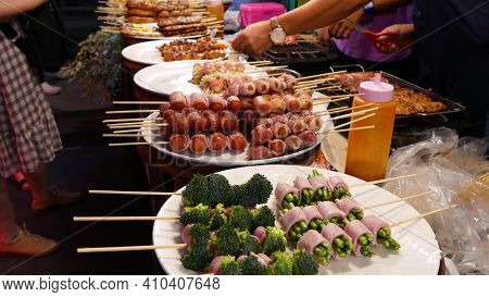 Traditional Asian Night Street Food Market In Thailand. Barbecue Meatballs And Other Exotic Deliciou