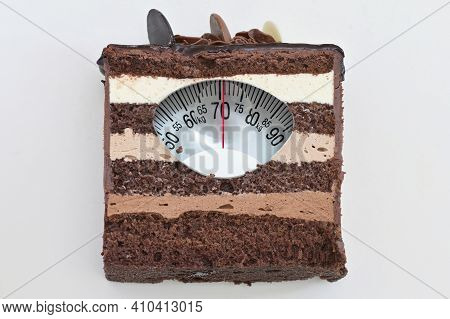 Conceptual Portion Of Chocolate Layer Cake And Weight Scale