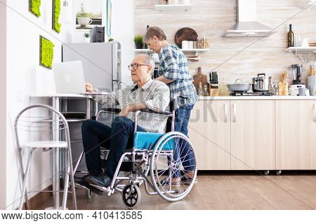 Paralysed Elderly Man In Wheelchair Typing On Laptop Working From Home At Computer In Kitchen While