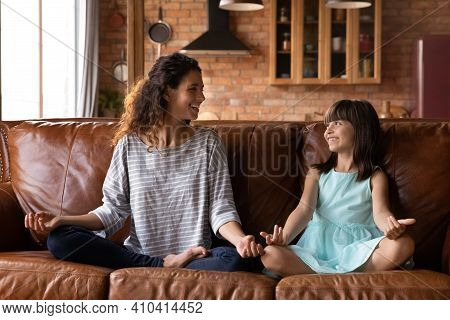 Happy Latino Mom And Little Girl Practice Yoga At Home
