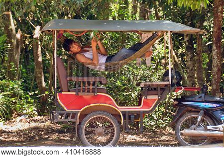 Angkor, Cambodia - Aug 28, 2013: Side View Of Man Chilling In Hammock Of Tourist Carriage Outdoors I