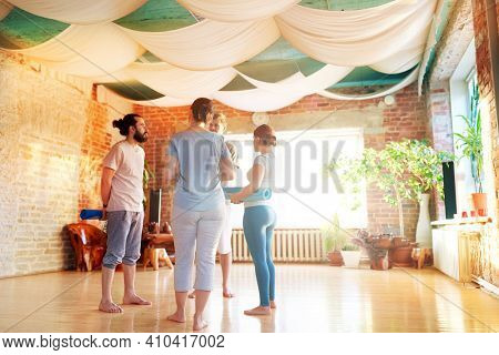 fitness, sport and healthy lifestyle concept - group of people with mats at yoga studio or gym