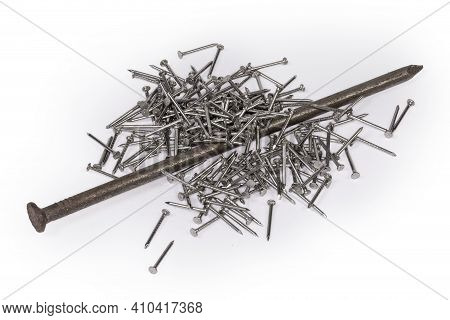 One Big Common Nail Lies On A Pile Of Small Nails With White Anti Corrosion Coating On A White Surfa