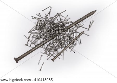 One Big And One Medium Size Common Construction Nails Lie On A Pile Of Small Nails With White Anti C