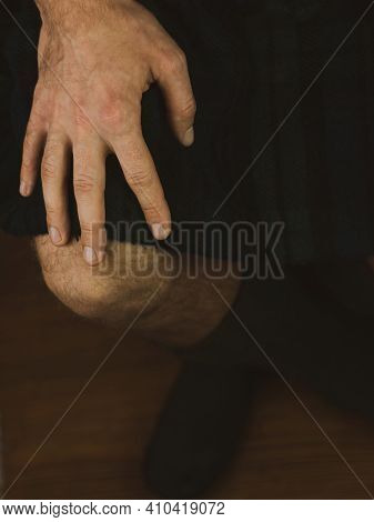Irish Man In Traditional Green Kilt With Hand On Knee. Scottish Guy Celebrating St. Patrick's Day In