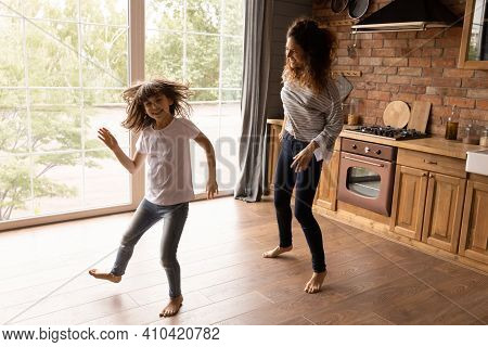 Overjoyed Latino Mom And Daughter Dance At Home