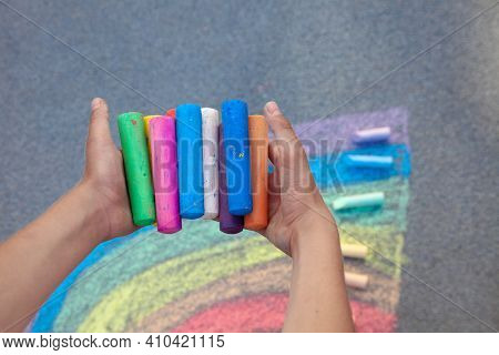 Chalks. Large Multi-colored Crayons In Children's Hands. The Child Holds The Chalk. Draw On The Stre