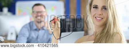 Young Beautiful Woman With Glasses In Hand With Partner In Background. Teamwork Meeting Concept.