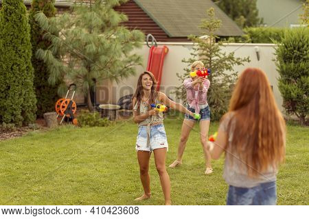 Group Of Young Friends Having Fun Spending Summer Day Outdoors, Playing With Water Guns, Splashing W