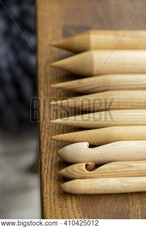 Assorted Wooden Knitting Needles Lie On A Wooden Table, In The Background A Blurred Gray Plaid Merin
