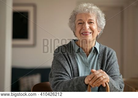 Portrait of smiling mature woman holding walking stick and sitting on chair at home. Portrait of happy senior woman under quarantine during covid-19 pandemic smiling while looking at camera.