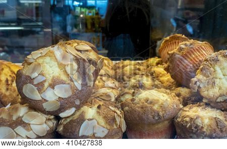 Small Vanilla Flavored Cupcakes Topped With Thinly Sliced Almond On Display For Sale In A Local Bake
