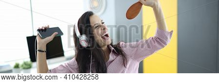 Woman In Headphones On Couch Holds Smartphone In Her Hands And Pretends To Sing. Emotional Energy Bo