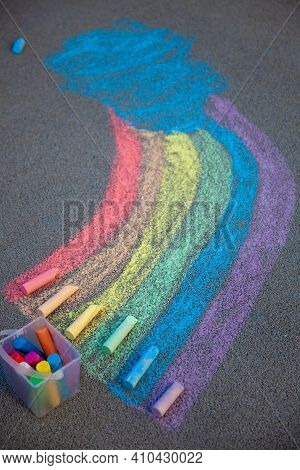 A Rainbow Painted On The Asphalt With Multicolored Large Crayons. Chalk And A Bucket Of Crayons. Lgb