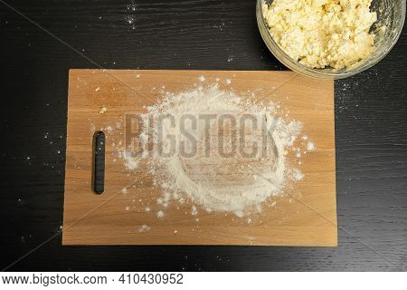 Wooden Board With Flour, A Bowl With A Mass For Cottage Cheese Pancakes Stands On A Black Table, Top