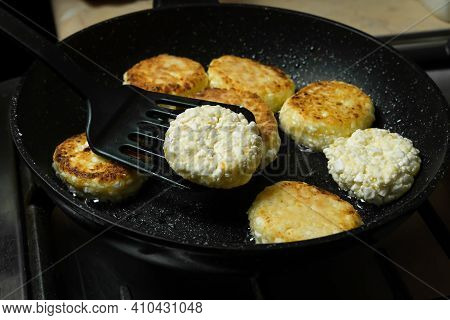 Cottage Cheese Pancakes Are Fried For Breakfast In A Black Pan Close-up. Flipping Cottage Cheese Pan