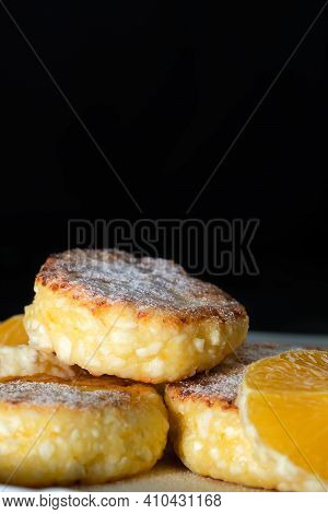 Sweet Cottage Cheese Pancakes With Orange Slices On A White Plate Close-up Against A Black Wall With