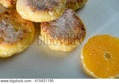 Delicious Cottage Cheese Pancakes With Powdered Sugar, With An Orange On A White Plate Close-up