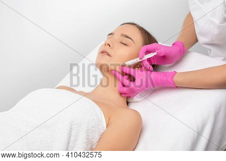 Cosmetologist Makes Lipolytic Injections To Burn Fat On The Chin, Cheeks And Neck Of A Woman Against