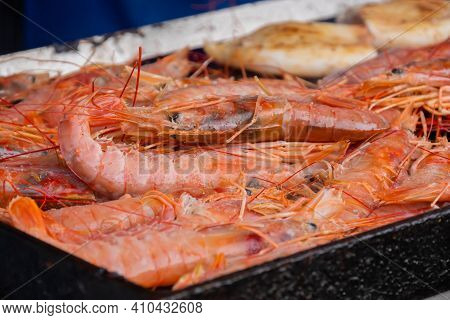 Process Of Cooking Fresh Red Langoustine Shrimps, Prawns And Squids On Grill At Summer Local Food Ma