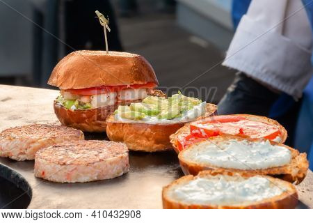 Process Of Preparing Burgers With Seafood, Fish Cutlet And Avocado On Brazier At Summer Local Food M