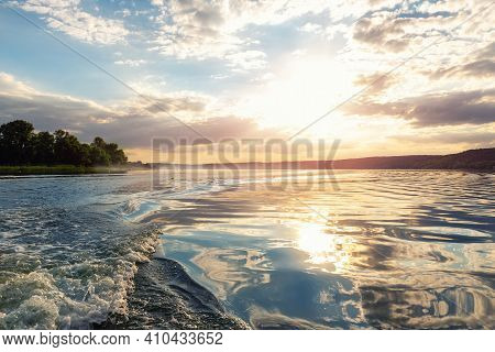 Scenic Bright Vibrant Blue To Red Warm Sunset Evening Time Landscape With Motorboat Swirl Trace On W