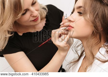 Make Up Artist Hands With A Lip Brush Paint And Apply Gloss On The Lips Of A Girl Bride