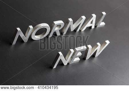 New Normal Word Composed Of Silver Metal Letters On A Flat Matt Black Surface With Diagonal Perspect
