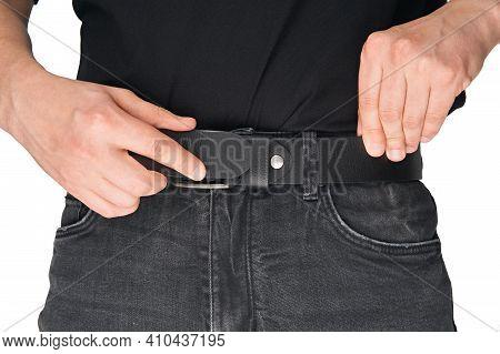 A Man In Black Jeans Puts On A Belt. Jeans Belt. Black Leather Belt. Buckle.