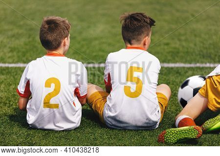 Boys In Soccer Jerseys With Golden Player Numbers On Back. Football Team Sitting On Sideline. Group