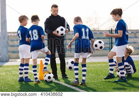 Young Coach Teaching Kids On Football Field. Trainer Explains To Schoolboys Training Rules. Football