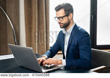 Serious Concentrated Determined Young Bearded Office Worker In Business Casual Clothes, Sitting At T