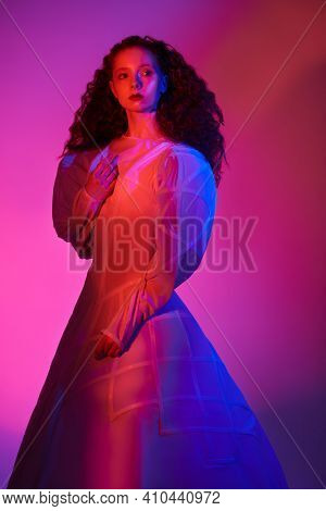 Fashion art. Portrait of a sophisticated female model with lush red curly hair posing in a white art dress. A studio portrait with mixed color light.