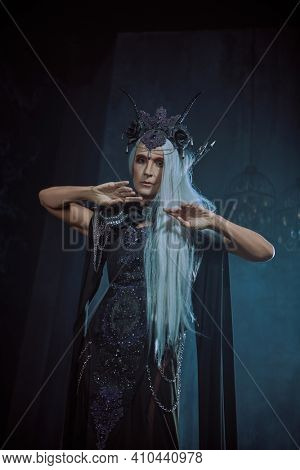 Stately and beautiful old woman with long gray hair, in a rich headdress and black dress against a dark background. Black Queen, Witch. Halloween.