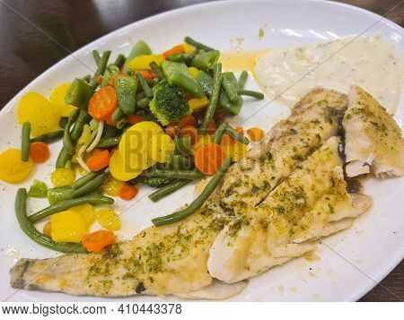 To Portions Of Fresh Grilled Pollock Or Coalfish Served With Colorful Salad And Slices Of Lemon, Clo
