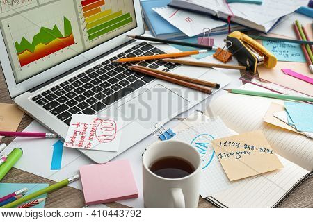 Laptop, Notes And Office Stationery In Mess On Desk. Overwhelmed With Work
