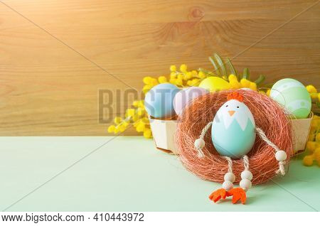 Easter background. Easter chicken and Easter eggs in the box near the mimosa flowers, free space for Easter text, Easter background, colourful Easter composition, Easter card, Easter pattern, Easter still life, Easter design