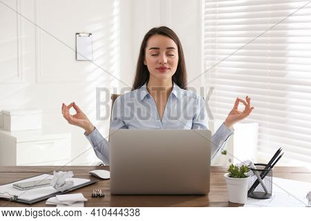 Businesswoman Meditating At Workplace In Office. Stress Relieving Exercise