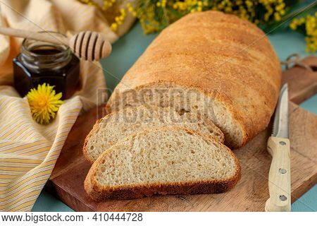 A Loaf Of Homemade Healthy Wholewheat Bread On A Serving Board Served With Honey And Mimosa