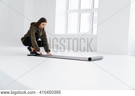 Athletic pleased sportswoman unrolling fitness mat before practice indoors