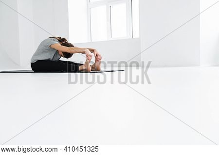 Athletic young sportswoman doing exercise while working out on mat indoors