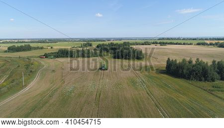 Combine Harvester At Work Harvesting Field Wheat. Aerial View Combine Harvester Mows Ripe Spikelets,