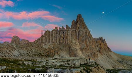 Evening in the Alps mountains. Panoramic landscape of Tre Cime di Lavaredo at night with real moon and clouds. Dolomites Alps, Italy