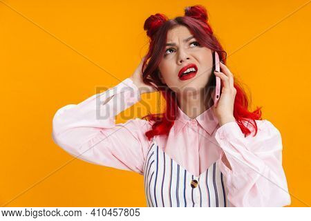 Displeased girl with red hair talking on mobile phone isolated over yellow background
