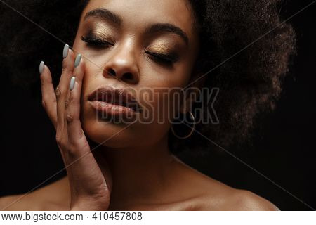 African american shirtless woman stroking her face while posing on camera isolated over black background